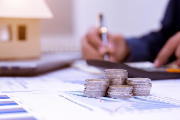 Homme d'affaires calculant l'impôt par maison modèle et piles de pièces sur la table.