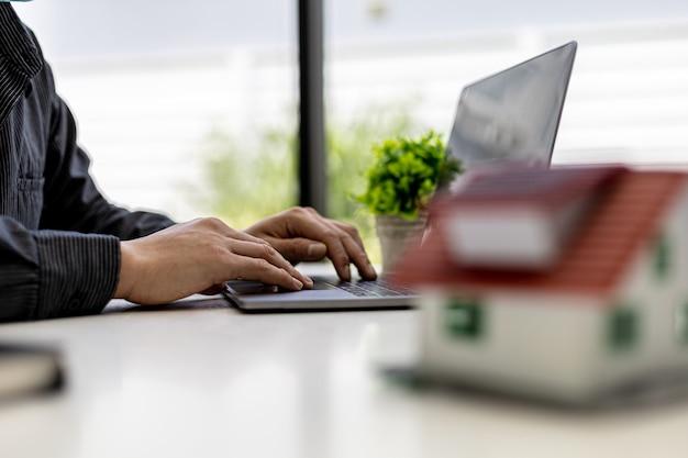 L'homme d'affaires calcule le montant sur un document de vente de lotissement sur ordinateur portable, il rencontre le directeur des ventes pour placer une vente et faire des promotions, des plans marketing pour augmenter les ventes