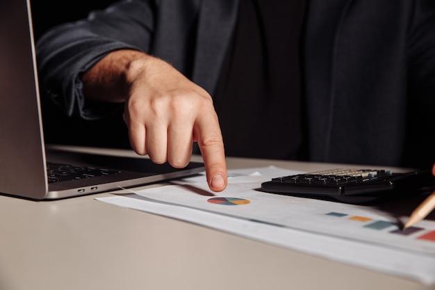 Homme d'affaires calcule le profit et regarde dans le graphique