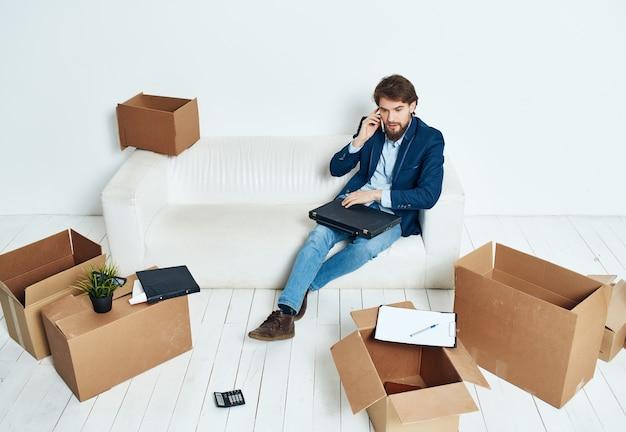 Homme d'affaires sur le canapé avec des boîtes transportant des choses nouveau lieu de travail