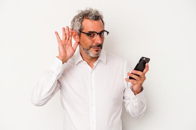 Homme d'affaires caucasien d'âge moyen tenant un téléphone portable isolé sur fond blanc essayant d'écouter un potin.