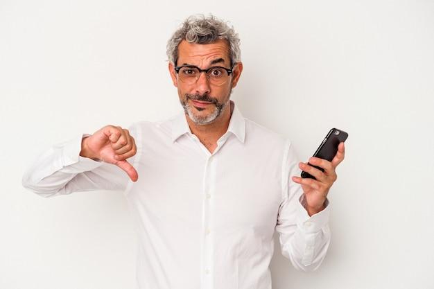 Homme d'affaires caucasien d'âge moyen tenant un téléphone portable isolé sur fond blanc montrant un geste d'aversion, les pouces vers le bas. notion de désaccord.