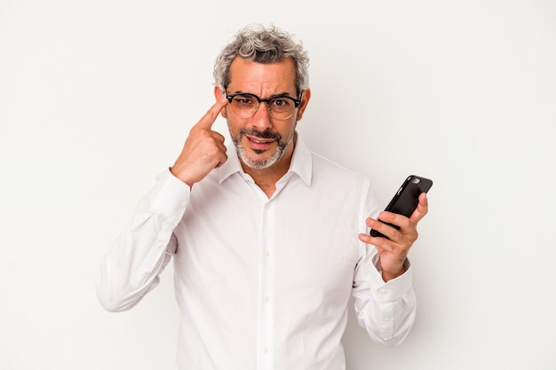 Homme d'affaires caucasien d'âge moyen tenant un téléphone portable isolé sur fond blanc montrant un geste de déception avec l'index.
