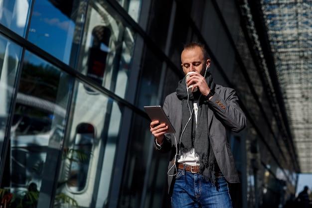 Homme d'affaires caucasien attrayant portant des vêtements décontractés marchant à l'extérieur, détient un ordinateur tablette et boit du café près du centre de bureau moderne. concept d'entreprise.