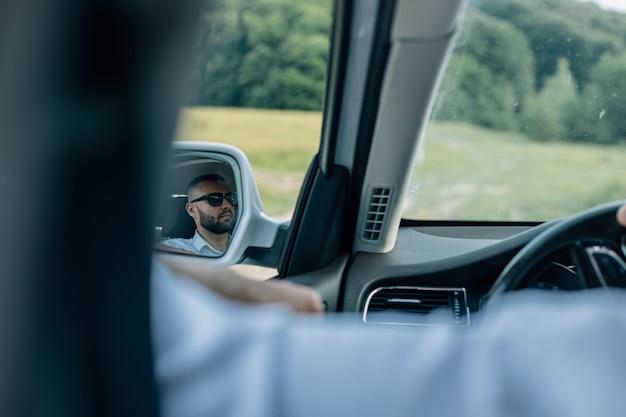 Homme d'affaires caucasien barbu regardant la caméra à travers la tête et les épaules du rétroviseur