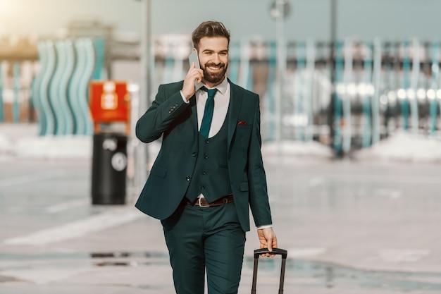 Homme d'affaires caucasien barbu souriant en tenue de soirée, parler au téléphone et tirer des bagages tout en marchant sur le parking.