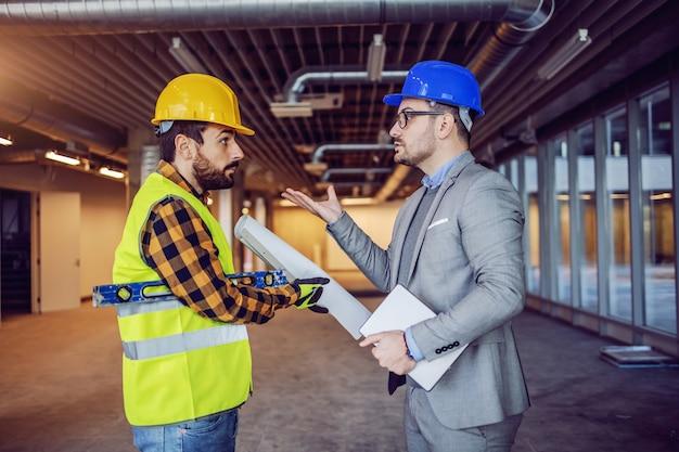 Homme d'affaires caucasien en colère en costume et casque sur la tête se disputant avec un travailleur de la construction irresponsable. bâtiment à l'intérieur du processus de construction.