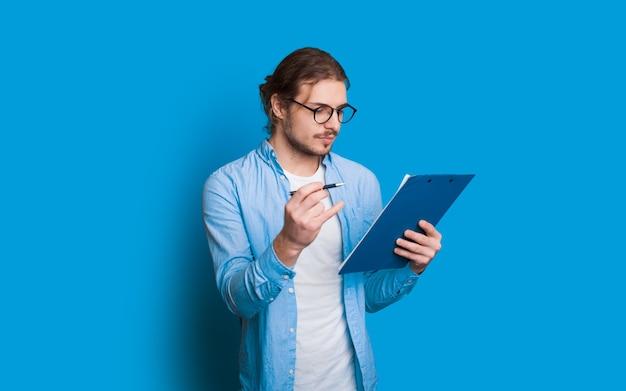 Homme d'affaires caucasien confiant habillé en bleu fait quelques avis dans son bloc-notes tout en posant sur un fond bleu