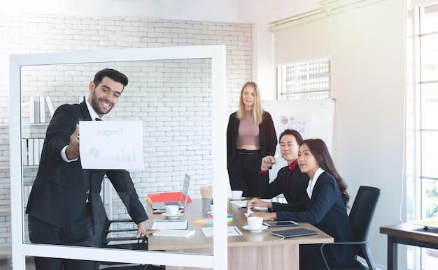 Homme d'affaires caucasien donnant une présentation sur le tableau de verre en séminaire d'entreprise avec un collègue multiethnique au lieu de travail.
