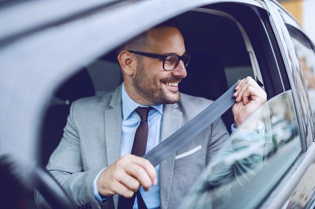 Homme d'affaires caucasien gai bouclant la ceinture de sécurité tout en étant assis dans sa voiture chère.
