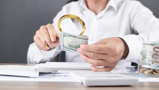 Homme d'affaires caucasien grossissant les billets en dollars.