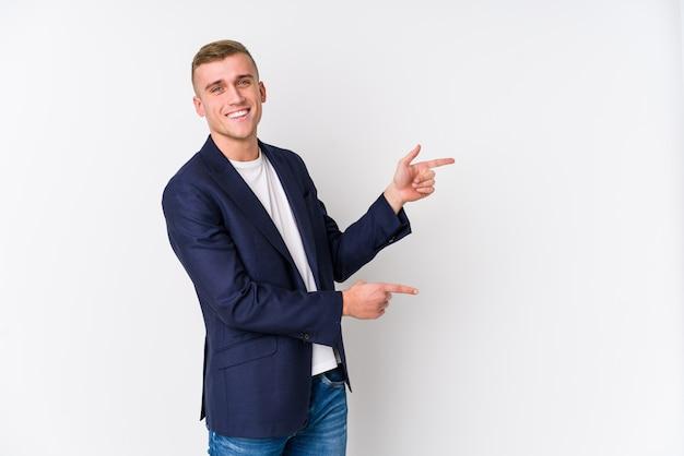 Homme d'affaires caucasien jeune excité pointant avec les index loin.