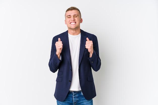 Homme d'affaires caucasien jeune levant le poing, se sentant heureux et réussi. concept de victoire.