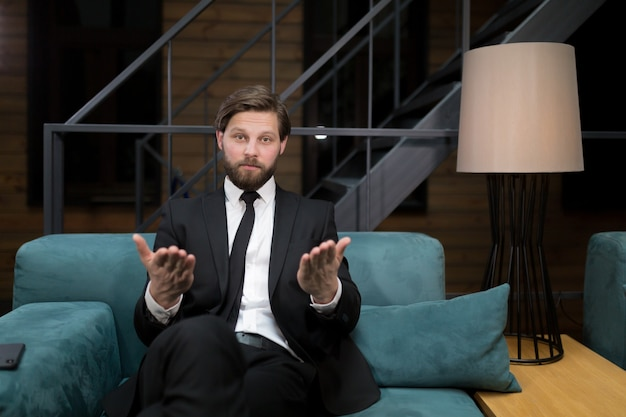Un homme d'affaires caucasien portant un costume et une cravate souriant à la caméra parlant lors d'une conférence commerciale en ligne expliquant les détails du contrat à un partenaire étranger via l'application de connexion