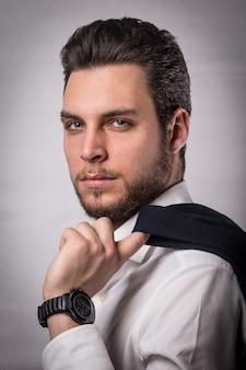 Un homme d'affaires caucasien pose vêtu d'une chemise blanche et se penche sur un élégant costume sur son épaule