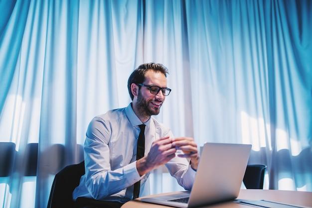Homme d'affaires caucasien satisfait souriant avec succès en chemise et cravate et avec des lunettes assis dans son bureau et lire des rapports.