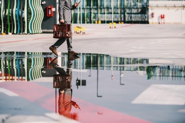 Homme d'affaires caucasien sophistiqué tenant une mallette et marchant sur une flaque d'eau sur le parking.
