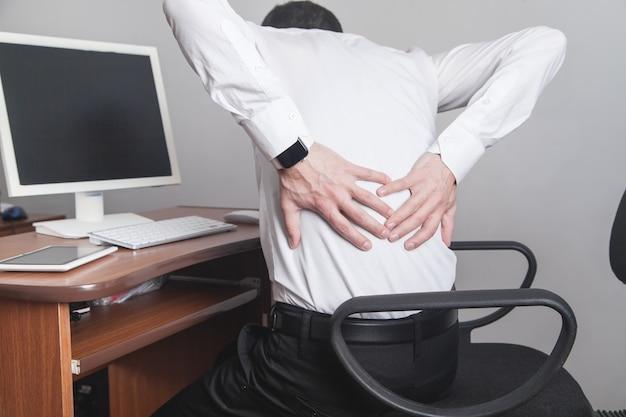 Homme d'affaires caucasien souffrant de maux de dos au bureau.