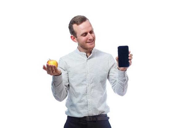 Homme d'affaires caucasien tenant un téléphone portable en noir et tenant une pomme rouge-jaune. il porte une chemise. portrait émotionnel. isolé sur fond blanc