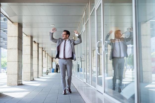 Homme d'affaires célébrant le succès au travail. dans une tablette à main et dans un autre téléphone intelligent.