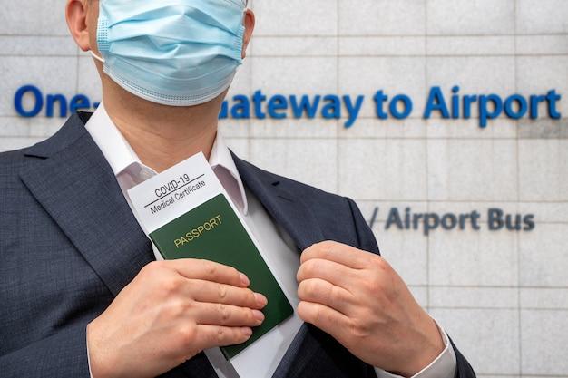 Un homme d'affaires avec un certificat de santé et un passeport pour le covid-19. concept d'entreprise post-covid-19.
