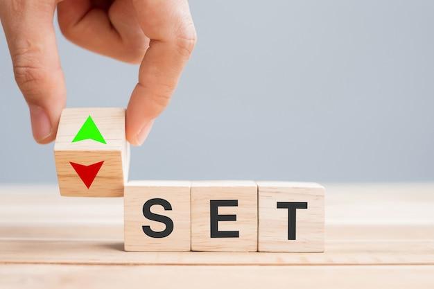 L'homme d'affaires change le bloc de cube en bois à la main avec le texte set (la bourse de thaïlande) vers l'icône de symbole de flèche haut et bas taux d'intérêt, actions, financier, classement, taux d'intérêt et concept de perte de coupe