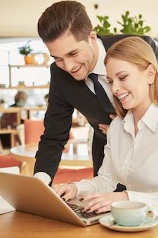 Homme d'affaires charmant aidant sa collègue, taper quelque chose sur son ordinateur