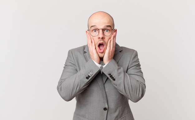 Homme d'affaires chauve se sentant choqué et effrayé, l'air terrifié avec la bouche ouverte et les mains sur les joues