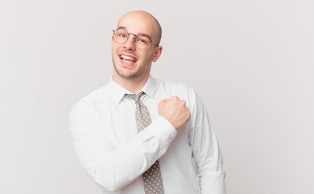 Homme d'affaires chauve se sentant heureux, positif et réussi, motivé face à un défi ou célébrant de bons résultats