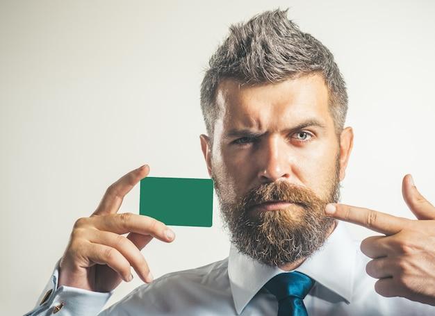 Un homme d'affaires en chemise blanche et cravate bleue montre une carte de crédit ou une carte de visite en gros plan sur une carte bancaire