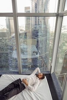 Homme d'affaires en chemise blanche est allongé sur un lit près d'une grande fenêtre panoramique au repos