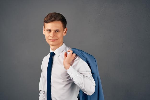 Homme d'affaires en chemise blanche avec veste cravate sur l'épaule studio