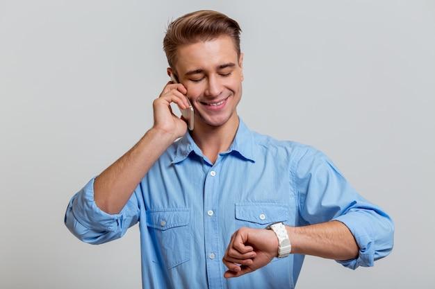 Homme d'affaires en chemise bleue souriant, parlant au téléphone.