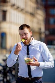 Homme d'affaires en chemise et cravate avec boîte à lunch salade