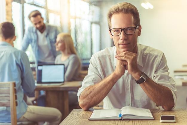Homme d'affaires en chemise et lunettes regarde la caméra