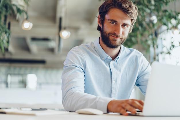 Homme d'affaires en chemise travaillant sur son ordinateur portable dans un bureau. bureau à aire ouverte
