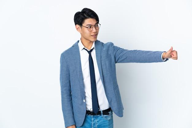 Homme d'affaires chinois avec isolé sur fond blanc donnant un geste de pouce en l'air