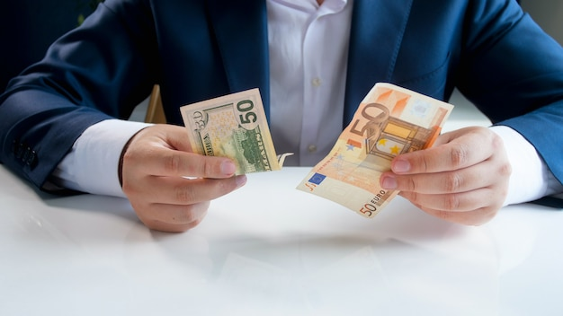 Homme d'affaires choisissant entre des billets en dollars et en euros.