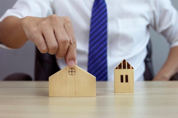 Homme d'affaires choisissant un modèle de maison en bois et envisageant d'acheter une propriété