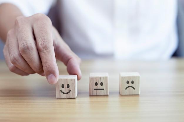 L'homme d'affaires choisit l'icône de visage souriant sur le cube en bois