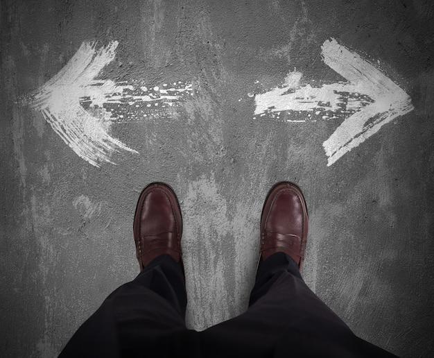 Homme d'affaires choisit quelle flèche blanche directionnelle suit