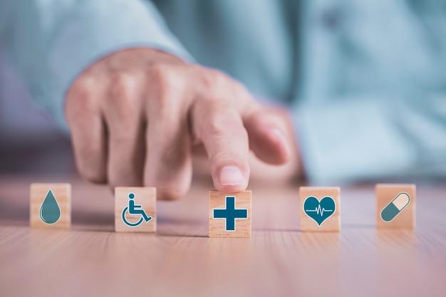 Homme d'affaires choisit un symbole médical de soins de santé icônes émoticône sur bloc de bois, concept d'assurance santé et médicale
