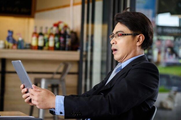 Homme d'affaires choqué après avoir lu des nouvelles sur une tablette