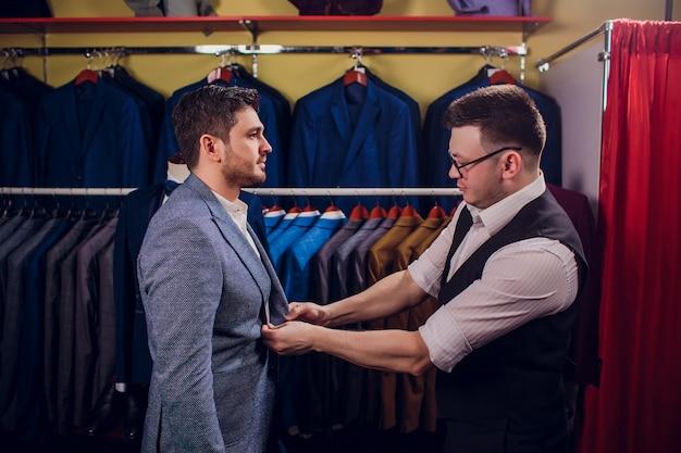 Homme affaires, classique, gilet, contre, rang, costumes, magasin un homme aide un autre à essayer un costume dans un magasin de vêtements