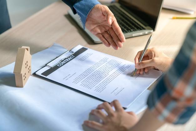 Homme d'affaires et client à la maison acheteur avaient réalisé et signé dans le contrat de l'immobilier