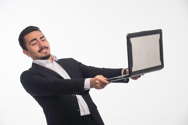 Un homme d'affaires en code vestimentaire tenant un ordinateur portable et ayant une réunion en ligne.