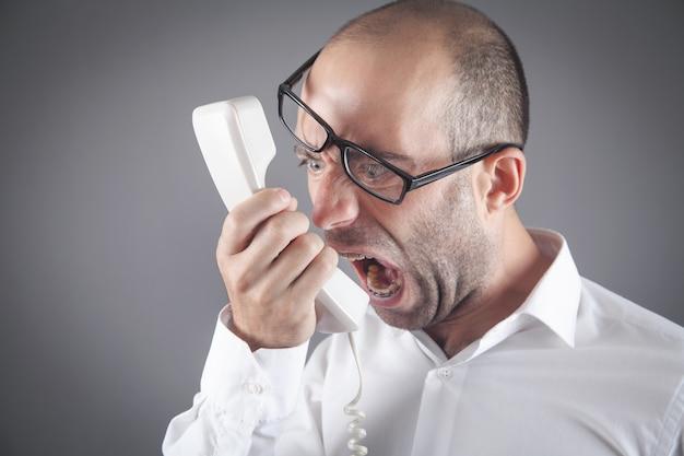 Un homme d'affaires en colère caucasien crie dans le récepteur téléphonique.