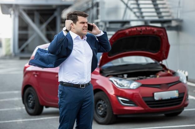 Homme d'affaires en colère criant au téléphone à cause d'une nouvelle voiture cassée