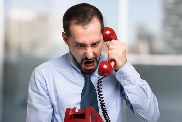 Homme d'affaires en colère criant au téléphone