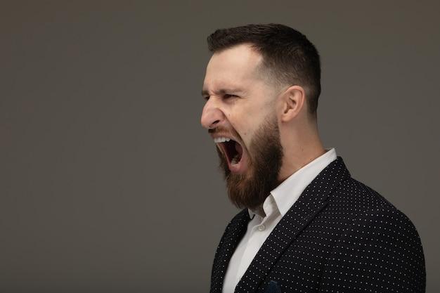 Homme d'affaires en colère criant. homme barbu criant sur le mur gris.